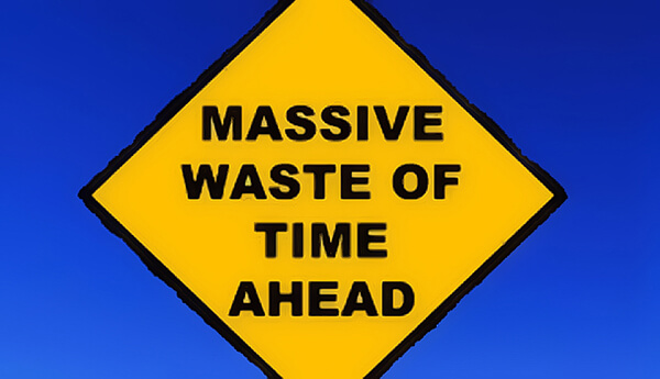 "A photo of a yellow street sign saying ""massive waste of time ahead"""